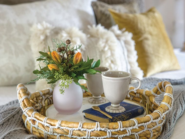 tea cup on tray on bed