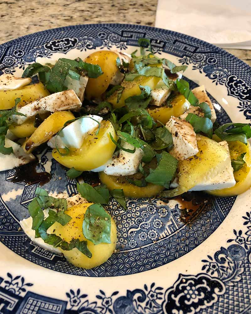 caprese salad with yellow peach tomato
